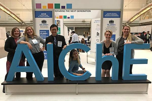 students in front of AICHE logo