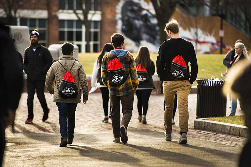 New students wearing their Husky 101 backpacks walk through Centennial Common