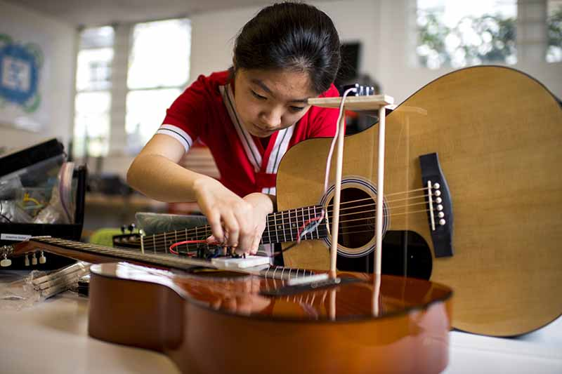 Student works to adapt a guitar to enable a person to play a guitar with limited movement on one side of their body.