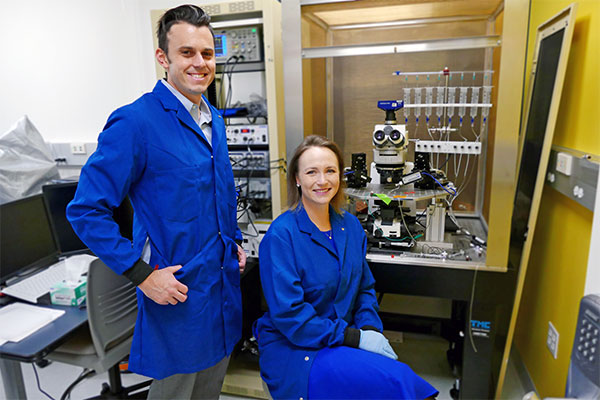 male and female professor posing in their chemical engineering lab with microscope in background