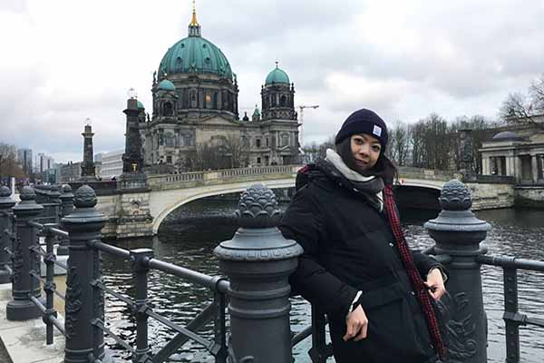 student in winter hat and coat posing in Berlin with building architecture of location in background on water