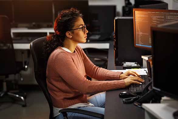 Female programmer working on new project. She working late at night in her office for ms in software engineering systems