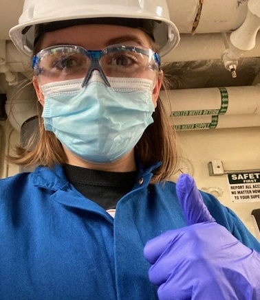student in lab coat gloves and mask