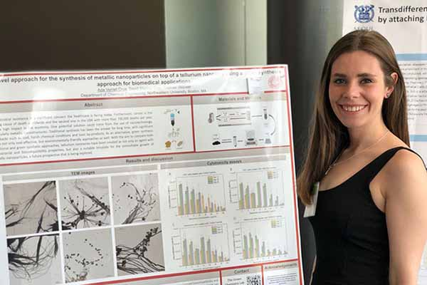 student smiling next to research poster on display