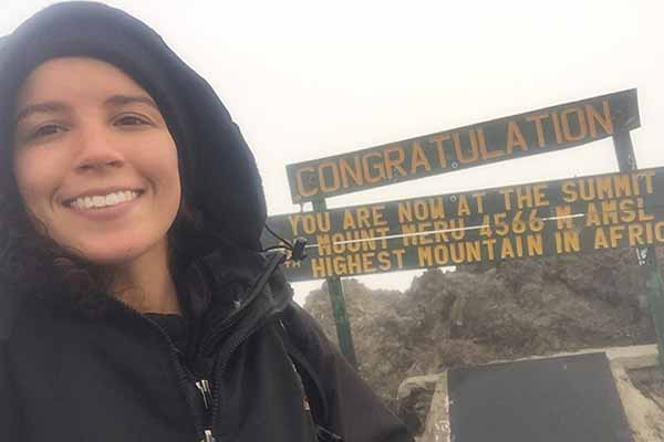 student on summit of mountain in africa