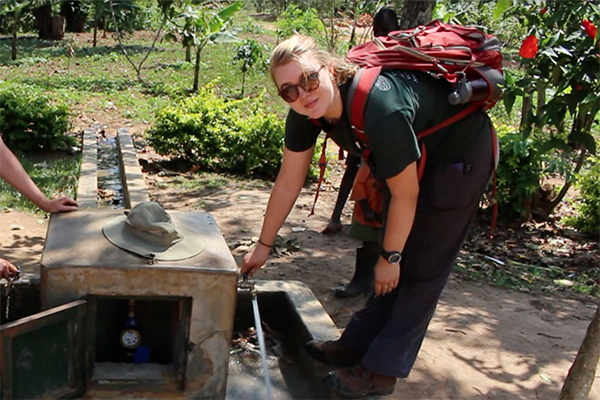 student learning over concrete water system in rural area abroad