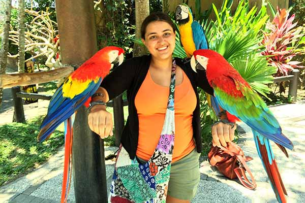 student with parrots on each arm smiling