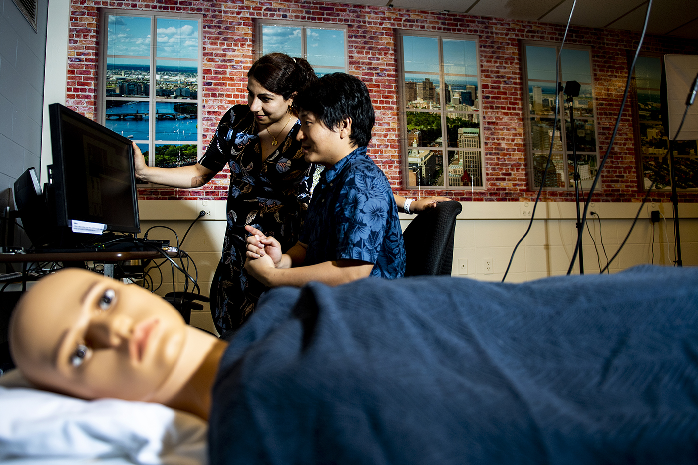 professor and researcher looking at monitor with manikin in bed