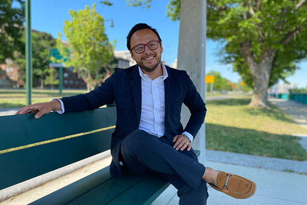 student posing outside sitting on a bench