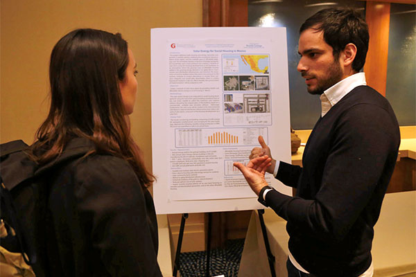 Ricardo Careaga speaking to a student in front of his research poster