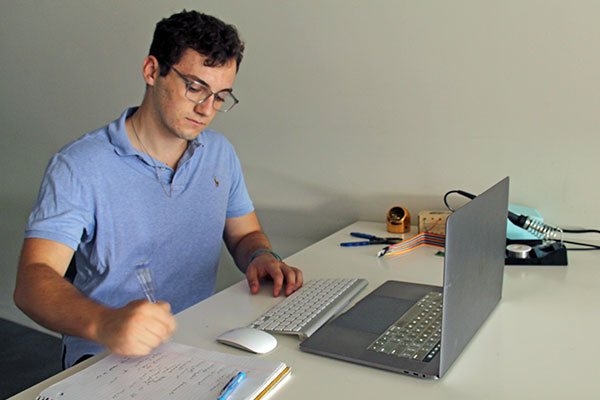student on co-op working at desk with laptop and writing