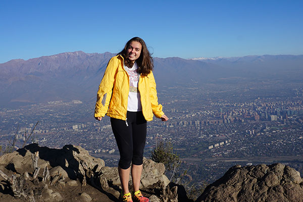 student overseas in Chile standing at top of mountain