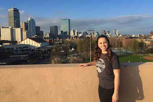 photo of student with Boston skyline in background