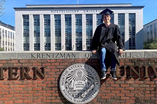 student sitting on Northeastern University wall in graduation attire