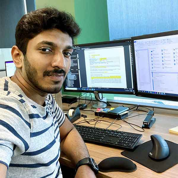 alumnus working at his job in front of double monitors