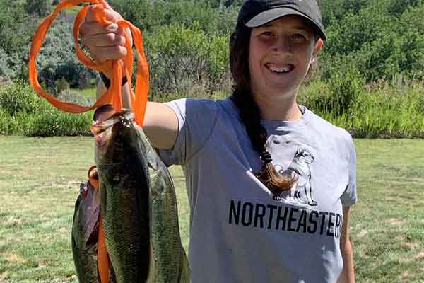 student holding up a few fish she caught