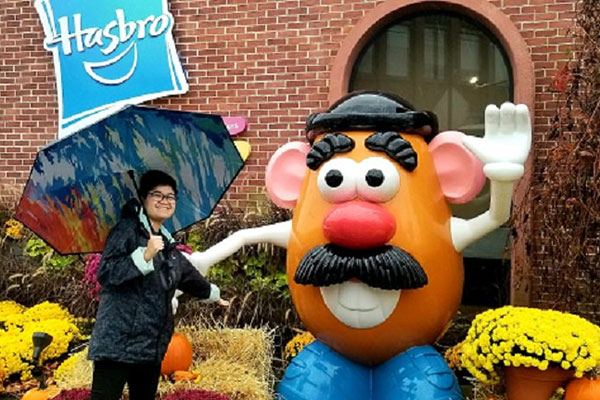 student on co-op posing with Mr. Potato Head at Hasbro