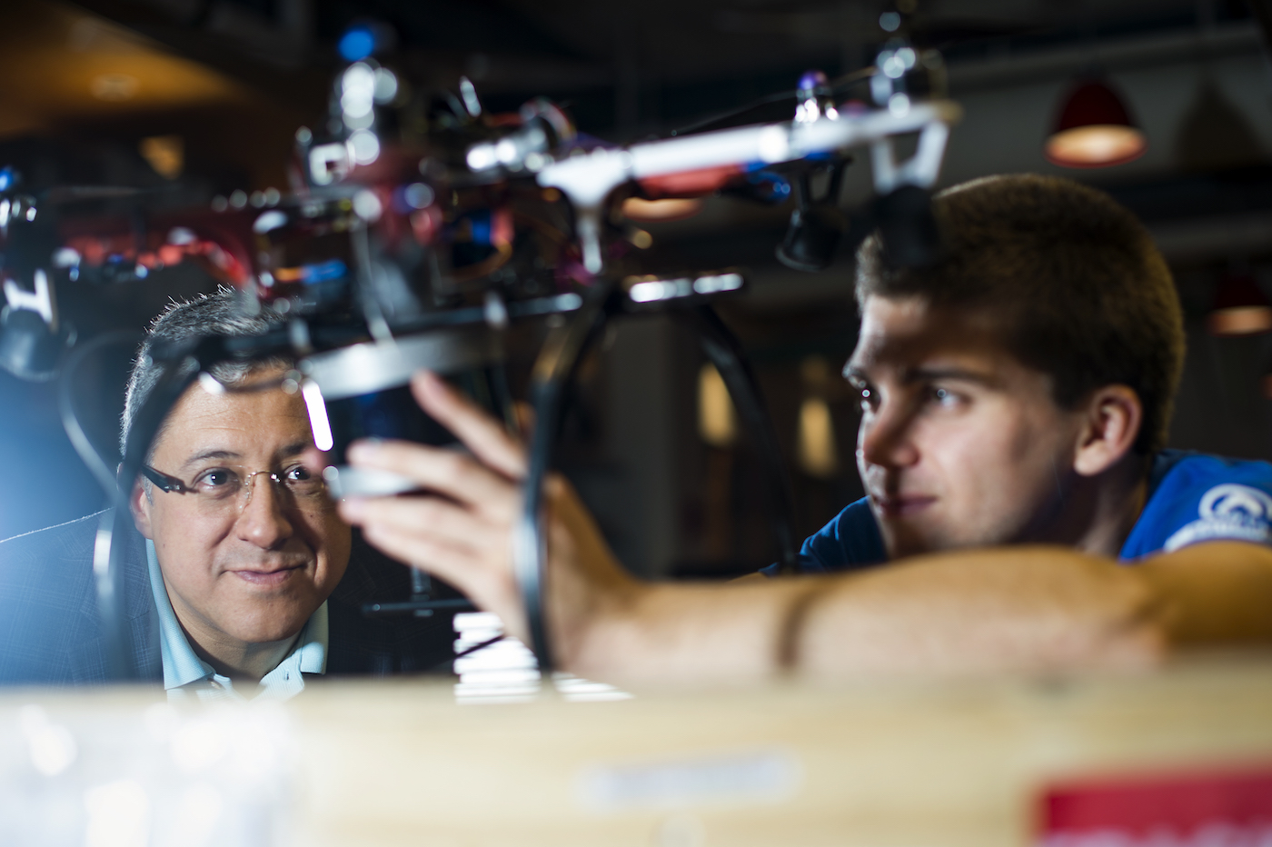 Taskin Padir and his student Nicolas Binford work on a hexi-copter drone. Padir's lab is developing aerial robots for damage detection after disasters. Photo by Adam Glanzman/Northeastern University