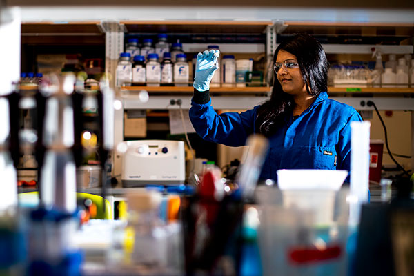 bajpayee looking at a vial in her lab