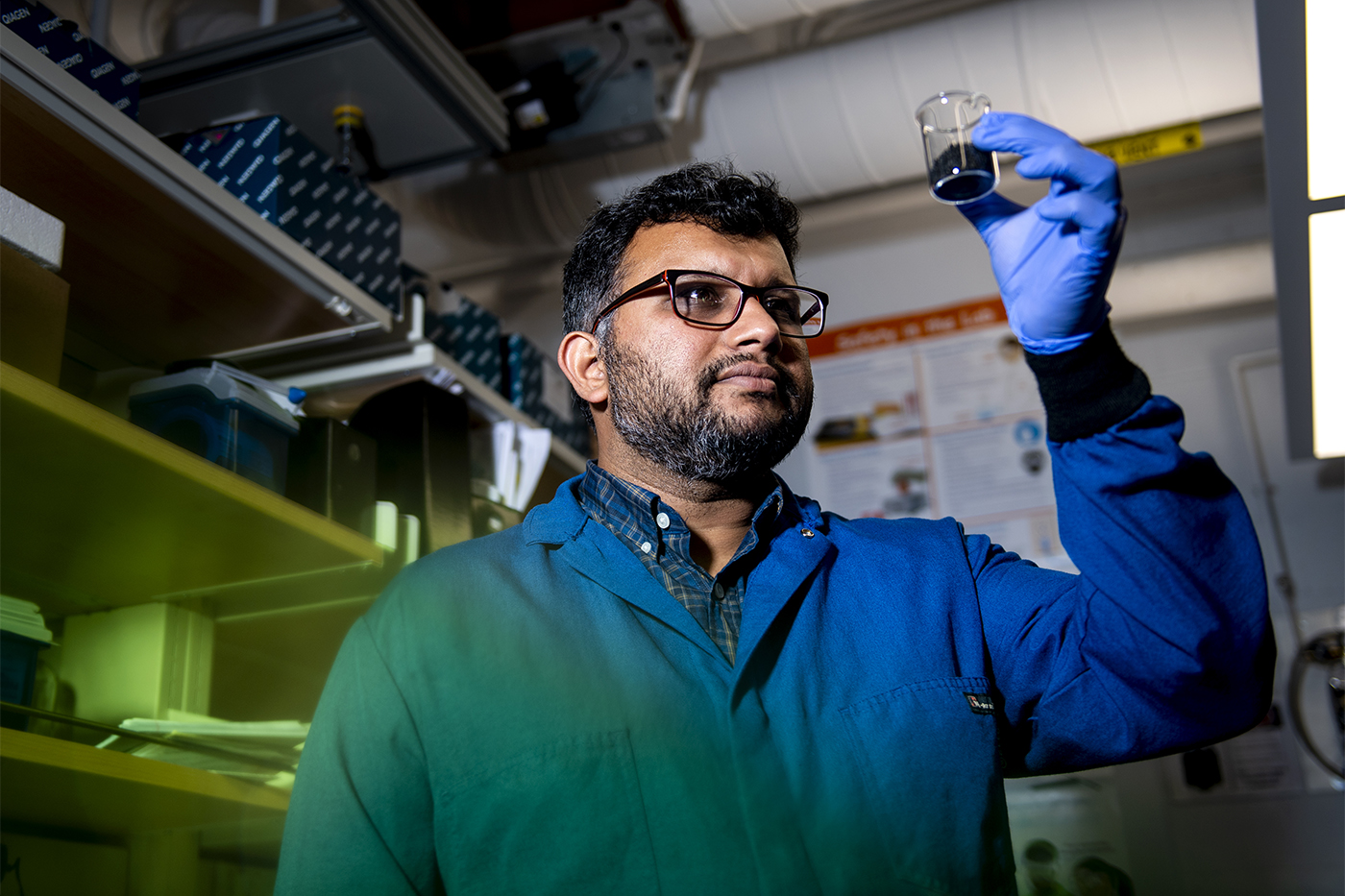 Ameet Pinto in environmental engineering lab holding up liquid