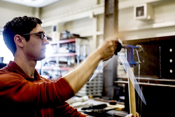 professor in lab turning a handle on wall equipment