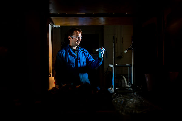 professor in lab looking at test tube