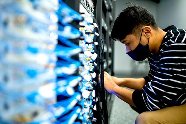 student works on wireless rack in data center