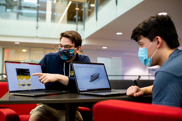 two students working on competition project on laptops