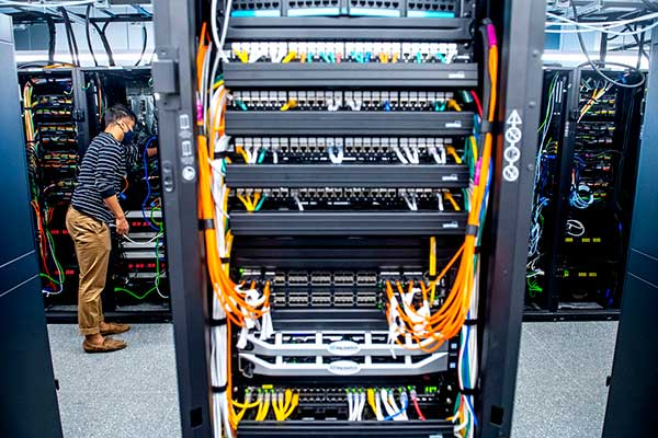 plugging network cables into the back of servers in big Colosseum data center