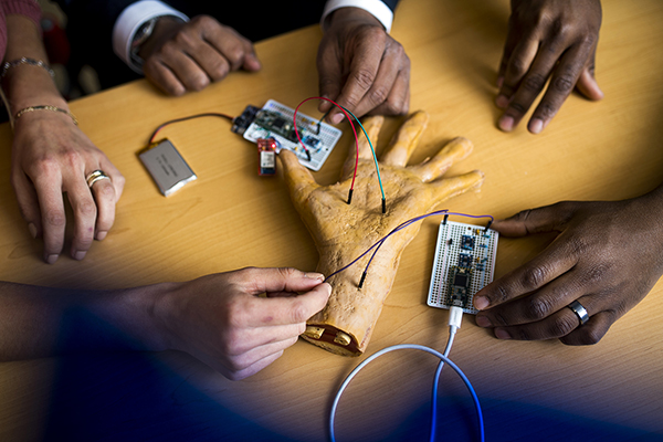 The hands of Stella Banou, Kaushik R. Chowdhury and William J. Tomlinson surround a robotic hand attached to circuits via wires.
