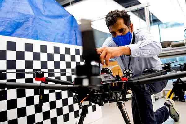 professor kneeling working on drone in lab