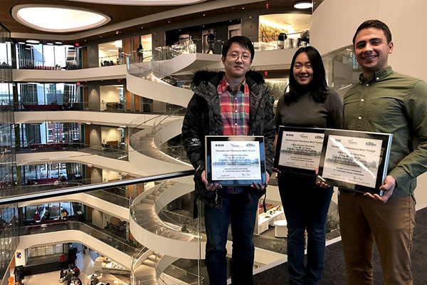 three students show their framed awards