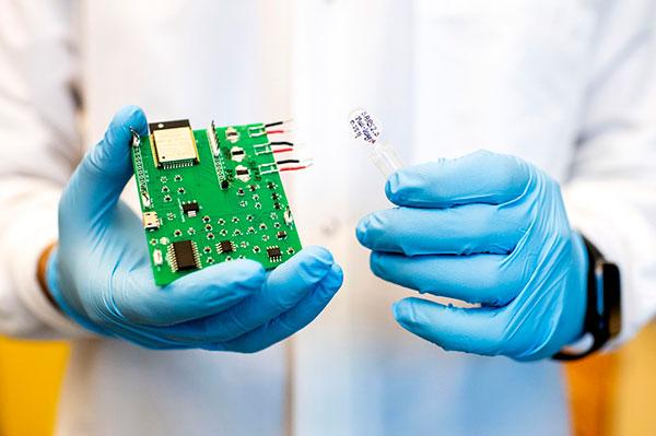 person in lab coat holding sensor