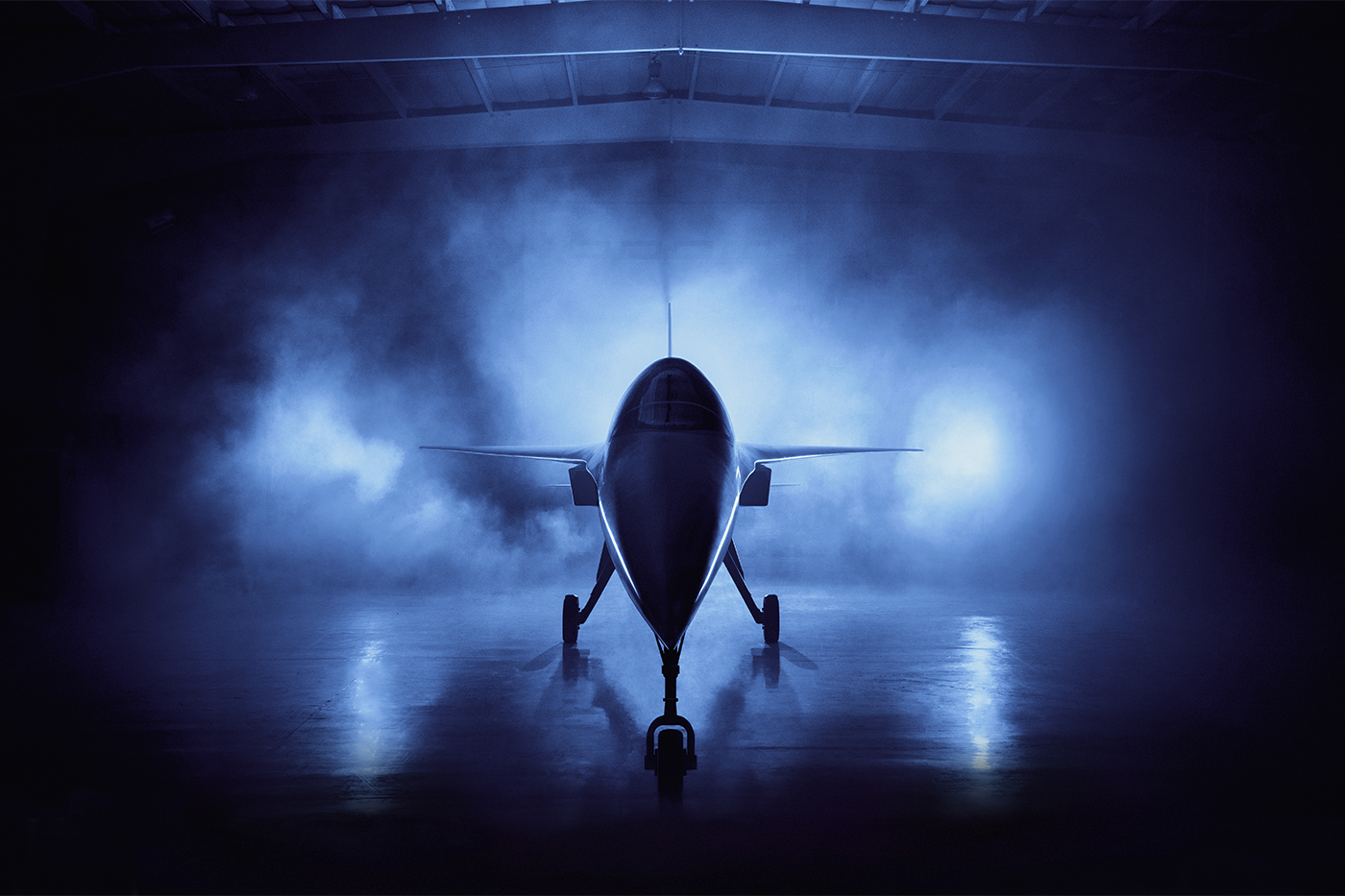A supersonic airplane sits in a hangar surrounded by fog and illuminated by blue light.