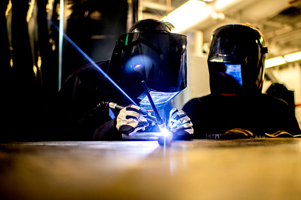 A student uses a laser to fabricate a race car.