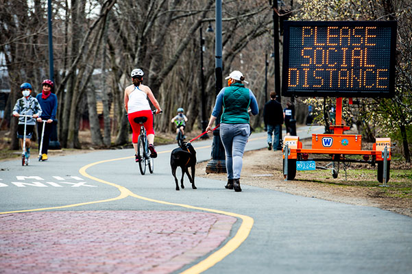 people walking and riding bike on walkway with please social distance digital sign