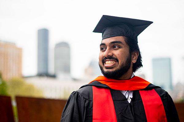 student in graduation attire smiling