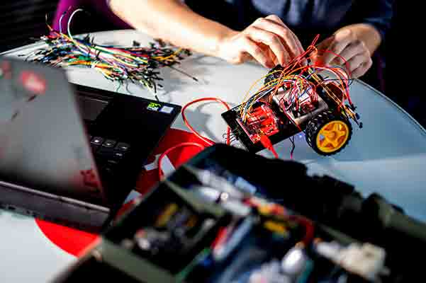student hands working on robotics project of model motorized vehicle