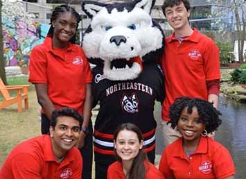 five students and a person dressed up as a husky mascot smiling