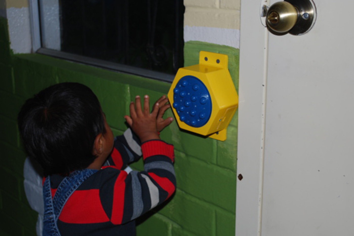 A kid at the For His Children Orphanage uses the communication button.