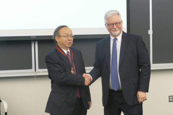 provost shakes hands with guest who has medal around neck