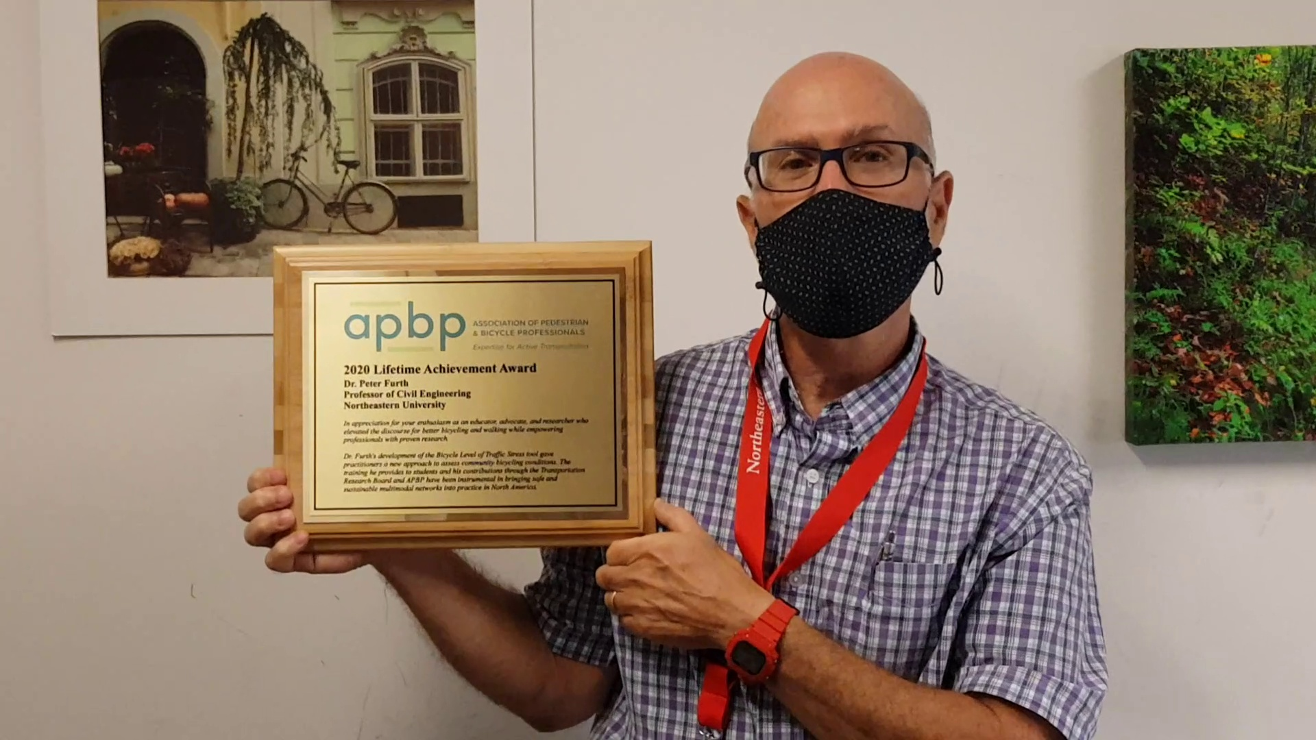 professor showing apbp award certificate