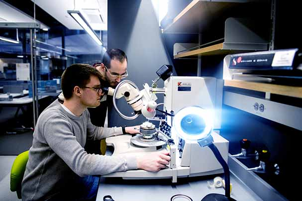 two students working in lab looking in microscope