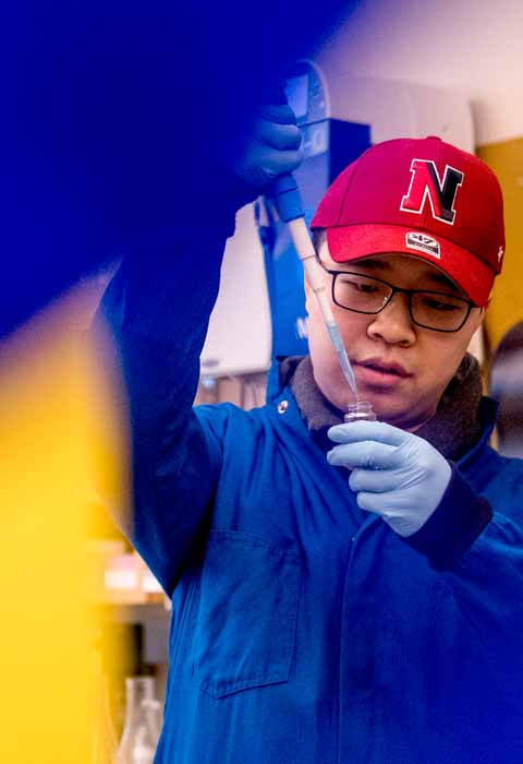 phd student squirting chemicals in small tube