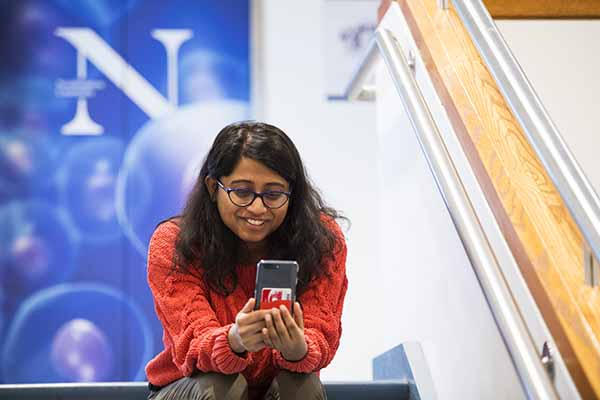 student sitting on stairs with the N logo in background and looking and smiling at mobile phone