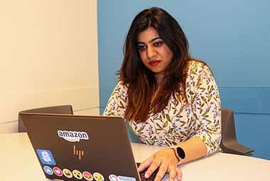 student on laptop with Amazon logo on back
