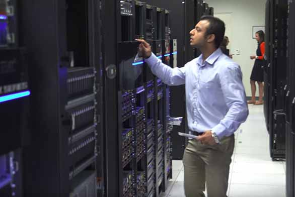 man working in data center pushing button on rack