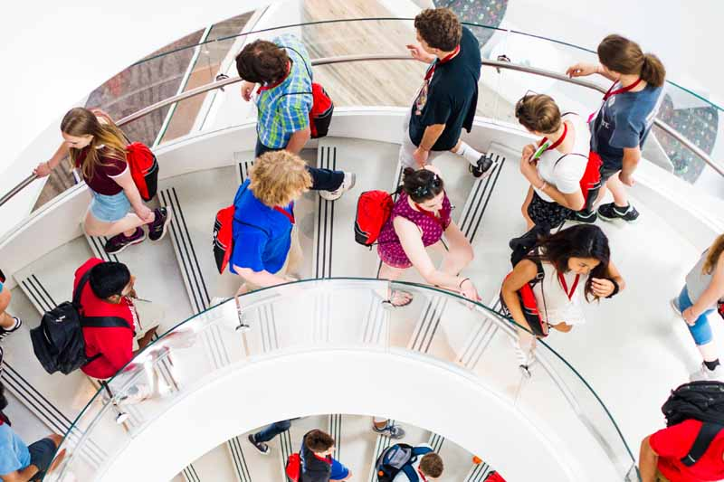 students with red bags walking together down spiral staircase